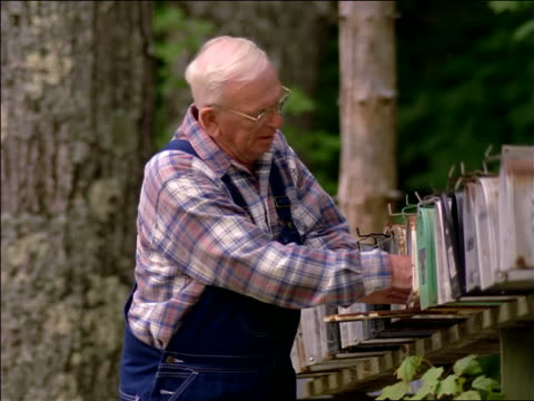 Senior man walking along long row of mailboxes, taking mail out of mailbox, reading letter + smiling