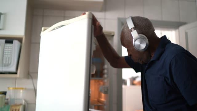 vídeos de stock, filmes e b-roll de idoso andando e ouvindo música em tablet digital em casa - geladeira