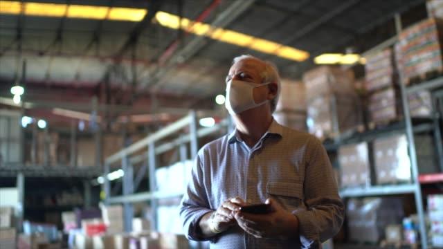 vídeos de stock e filmes b-roll de senior man walking and using mobile phone at warehouse - with face mask - controlo