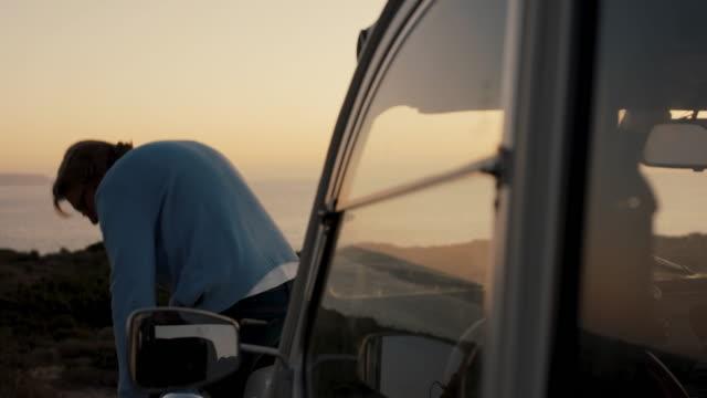 senior man walking around car, sitting down to look at ocean - portugal stock videos & royalty-free footage