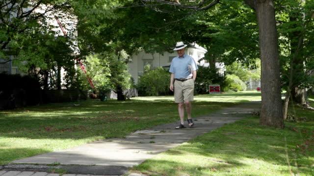 senior man walking in neighborhood - old newspaper stock videos and b-roll footage