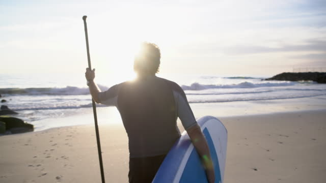 ms senior man walking into the sea holding his paddleboard - anziani attivi video stock e b–roll