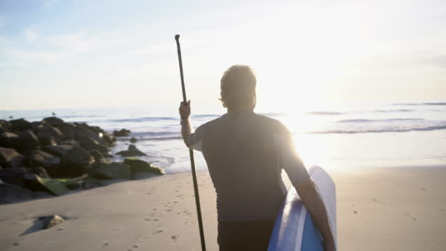 stockvideo's en b-roll-footage met ms senior man walking into the water with his paddleboard - surfbord