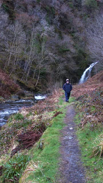 senior man walking on a path beside a river - johnfscott stock videos & royalty-free footage