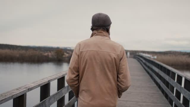 vídeos y material grabado en eventos de stock de senior man walking on estuary boardwalk - vista posterior