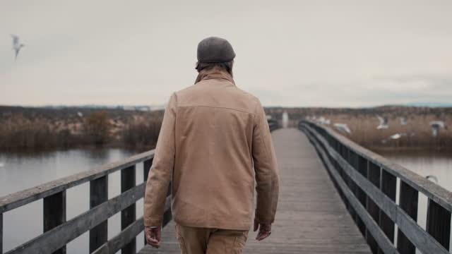 vídeos y material grabado en eventos de stock de senior man walking on estuary boardwalk with birds - incertidumbre