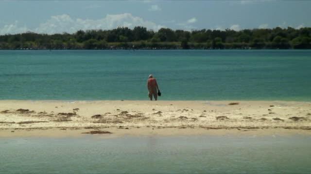 MS ZO PAN WS Senior man walking on sandbar, Coffs Harbour, New South Wales, Australia