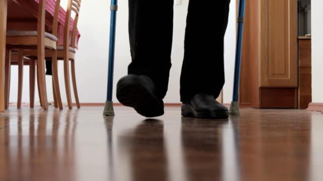 senior man walking past camera with crutch - crutch stock videos & royalty-free footage