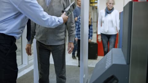 senior man walking through a metal detector at the airport and being scanned by a handheld metal detector - security stock videos & royalty-free footage
