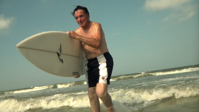 slo mo ms senior man walking through water carrying surfboard, jacksonville, florida, usa - young at heart stock videos & royalty-free footage