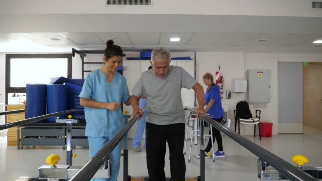 Senior man walking with difficulty using the parallel bars and therapist standing next to him helping