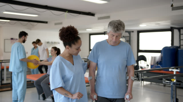 senior man walking with the help of crutches and female therapist assisting him very cheerfully. incidental patients at background - crutch stock videos & royalty-free footage