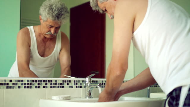 vídeos de stock e filmes b-roll de senior man washing hands - espelho