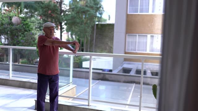 senior mann beobachten übungskurs auf laptop und stretching zu hause - menschliche gliedmaßen stock-videos und b-roll-filmmaterial