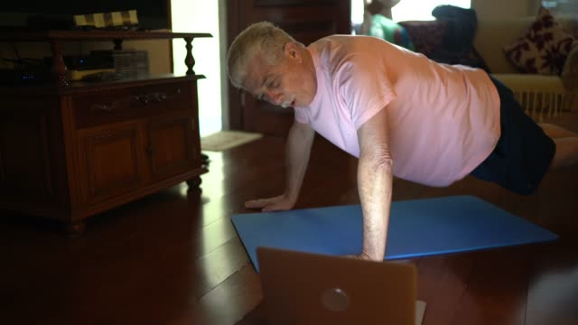 senior man watching gym class on laptop and doing exercises at home - senior men stock videos & royalty-free footage