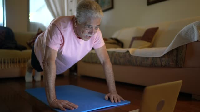 senior man watching gym class on laptop and doing exercises at home - net sports equipment stock videos & royalty-free footage
