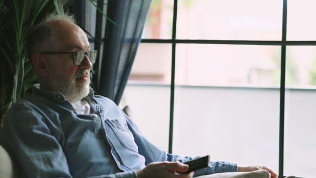 senior man watching tv at home - baby boomer stock videos & royalty-free footage
