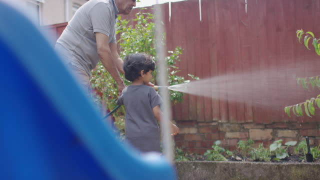 a senior man waters his garden with a hose pipe - david bond stock videos & royalty-free footage