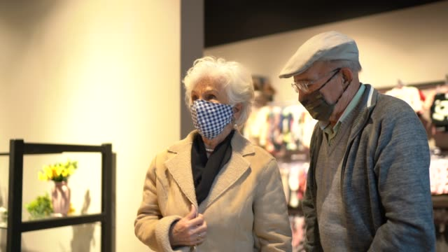 l'uomo anziano che indossa la maschera facciale aiuta la moglie a provare i cappotti in un negozio di parsimonia - casacca video stock e b–roll