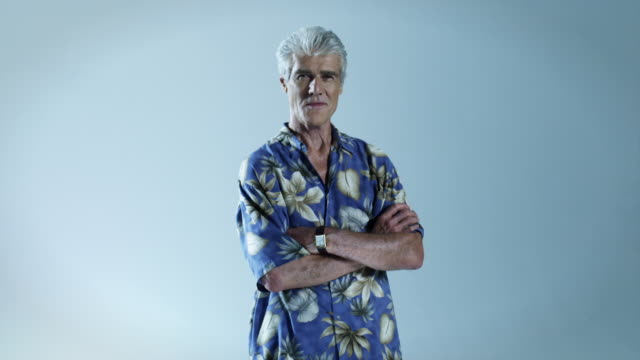 Senior man wearing hawaiian shirt with arms folded