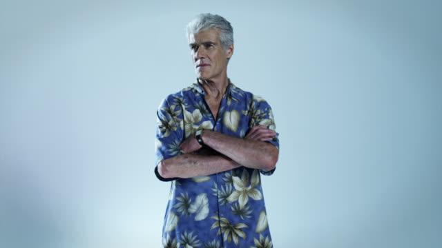 Senior man wearing hawaiian shirt with arms folded