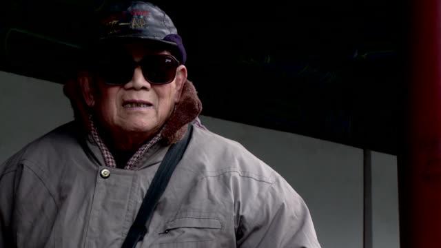 cu senior man wearing large sunglasses, beijing, china - baseballmütze stock-videos und b-roll-filmmaterial