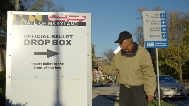 senior man wearing mask casts his vote in baltimore, maryland, on november 2, 2020. - servizio postale video stock e b–roll