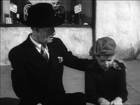 B/W 1938 senior man wearing suit + hat consoling depressed boy with hat on street curb