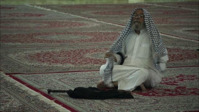 ms senior man wearing traditional clothing sitting on carpet at mausoleum of ayatollah khomeini, tehran, iran - auf dem boden sitzen stock-videos und b-roll-filmmaterial