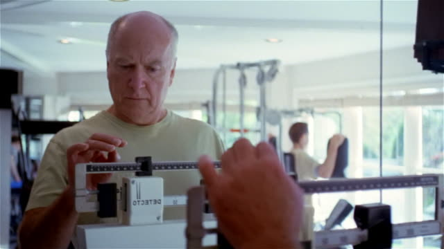 CU, senior man weighing himself on scale in gym, USA, Pennsylvania, Solebury