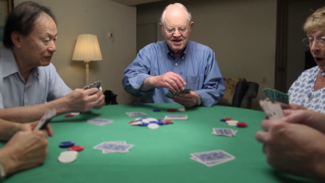 stockvideo's en b-roll-footage met senior man wins at card game - woongemeenschap ouderen