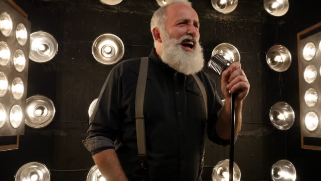 senior man with a beard singing with a microphone - singer stock videos & royalty-free footage