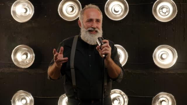 vídeos de stock e filmes b-roll de senior man with a beard singing with a microphone - artista