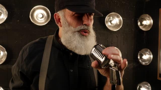 マイクを使ってひげの歌唱力を持つ年配の男性 - マイク点の映像素材/bロール