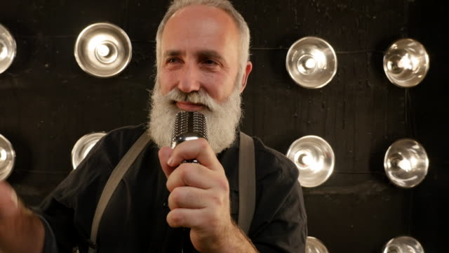 senior man with a beard singing with a microphone - passion stock videos & royalty-free footage