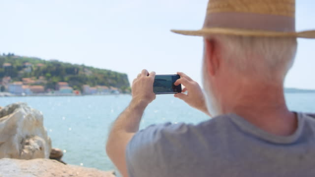 senior man with a grey beard and a summer hat taking photos of the beautiful coastal town on a sunny day - accessibility stock videos & royalty-free footage