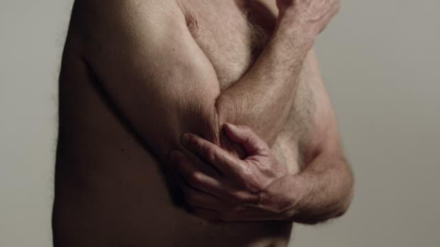 cu senior man with bare torso rubbing elbow / los angeles, california, usa - elbow stock videos & royalty-free footage