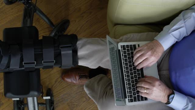 senior man with broken leg using a laptop at home - broken leg stock videos & royalty-free footage