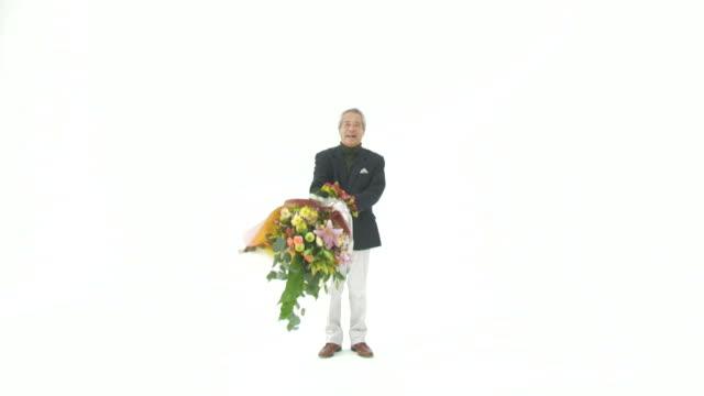 senior man with bunch of flowers - リタイアメント点の映像素材/bロール