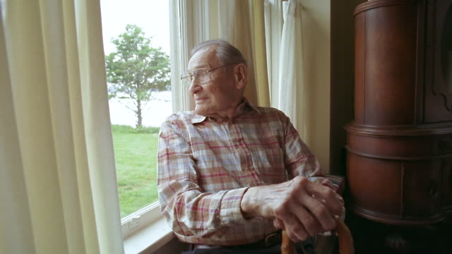 ms zi zo senior man with cane looking out window / washington state, usa - one senior man only stock-videos und b-roll-filmmaterial