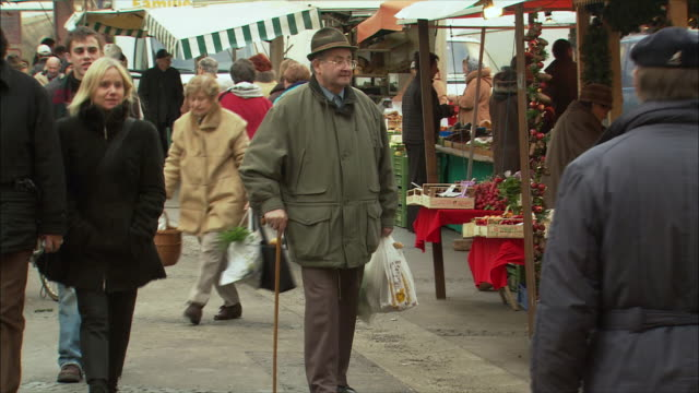 vidéos et rushes de ms pan senior man with cane walking through christmas market / salzburg, austria - austria