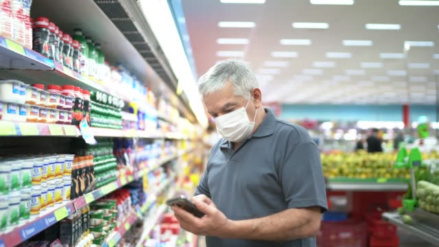vídeos de stock e filmes b-roll de senior man with disposable medical mask and his mobile phone shopping in supermarket - atividade comercial