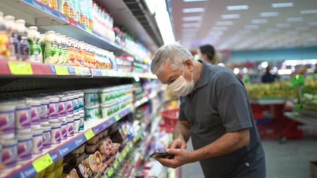 senior man with disposable medical mask and his mobile phone shopping in supermarket - calcium stock videos & royalty-free footage