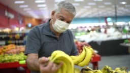 Senior man with disposable medical mask shopping in supermarket
