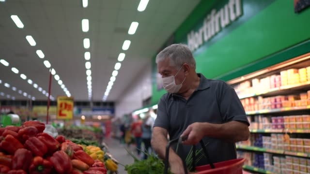 senior man with disposable medical mask shopping in supermarket - comprare video stock e b–roll
