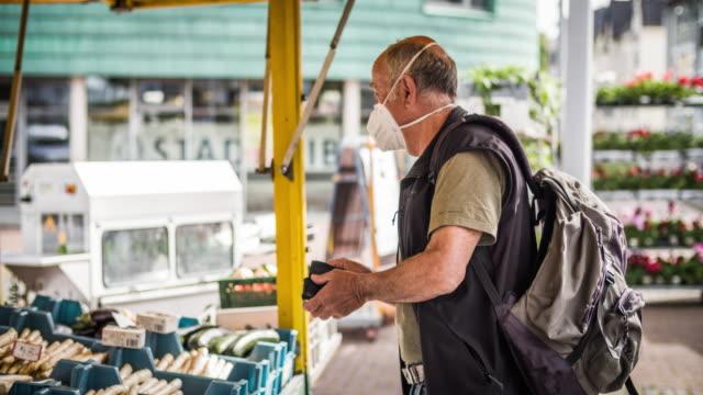 vidéos et rushes de homme aîné avec le masque de visage au marché d'alimentation - covid-19 - produit bio