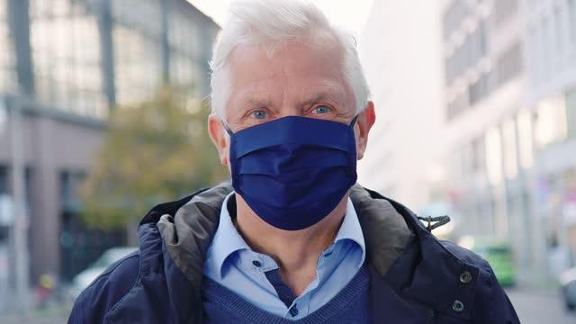 vidéos et rushes de homme aîné avec le masque principal dans la ville - manteau et blouson d'hiver