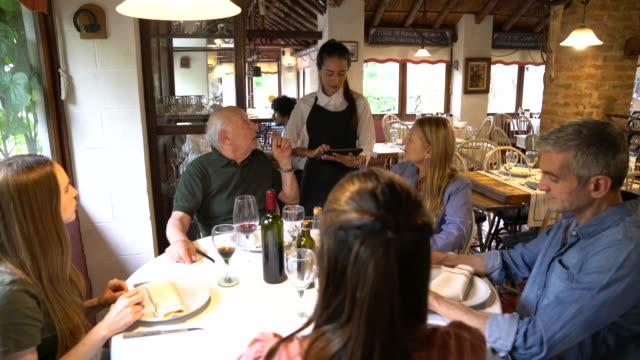uomo anziano con famiglia che dà ordine di pranzo al ristorante - ospite video stock e b–roll
