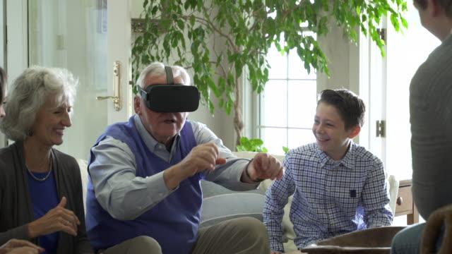 Senior man with family wearing virtual reality headset.