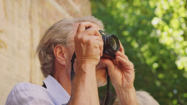 senior man with female using digital camera - tourism stock videos & royalty-free footage